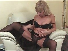 Mature light-haired Cathy Oakley strips to black undergarments